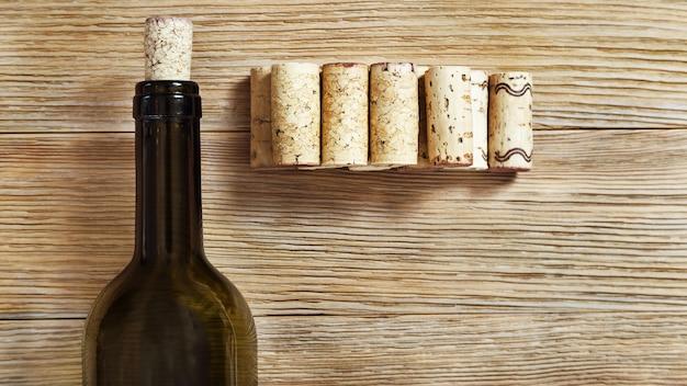 Темная бутылка вина с пробками на старой деревянной поверхности.