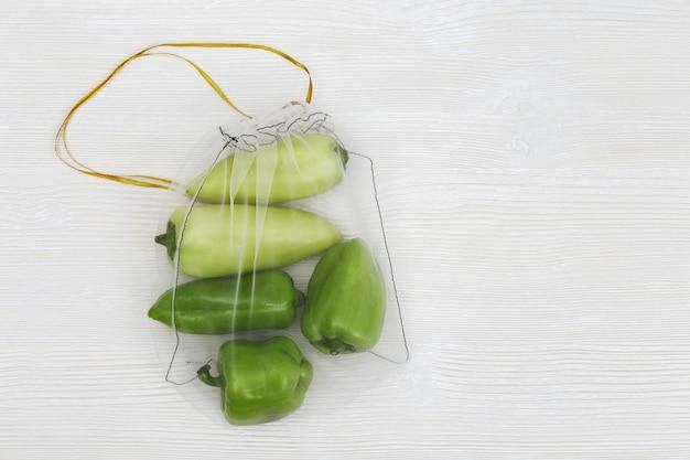 Зеленый перец в многоразовых эко-сумках. пластиковая бесплатная концепция.