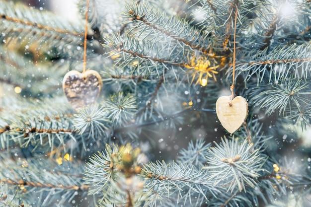 クリスマスの素朴な装飾は、外のクリスマスツリーに掛かっていると雪が降っているハートの形で自然な木のおもちゃ。