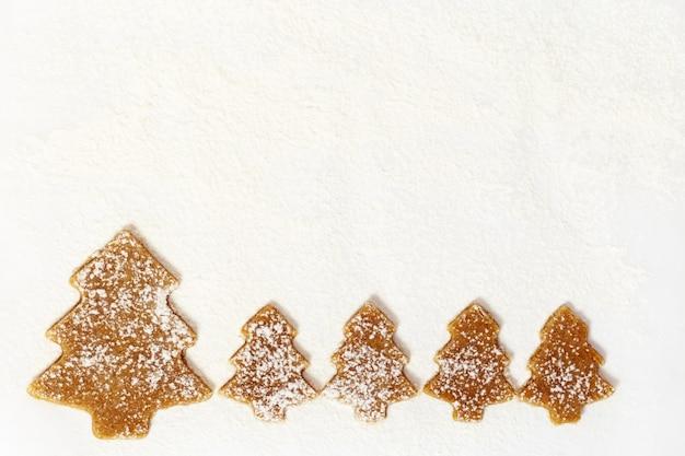 Имбирное печенье новогодний рисунок. печенье в форме елки на бумаге для выпечки. концепция праздника питания.