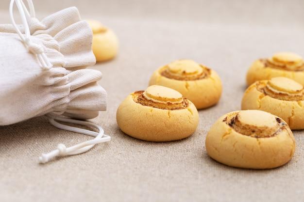 Нежное хрустящее печенье в форме грибов. запеченное сладкое печенье вылилось из мешка на текстильной поверхности.