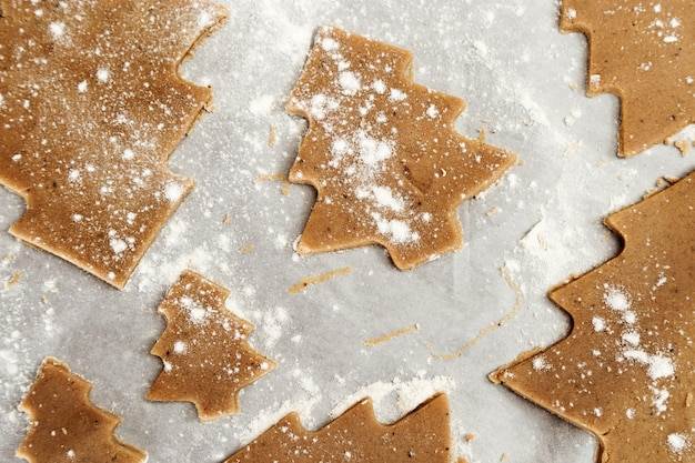 Имбирное печенье новогодние фигурки из теста, приготовленного для запекания в духовке. печенье в виде елки на бумаге для выпечки. рождественская еда концепция.
