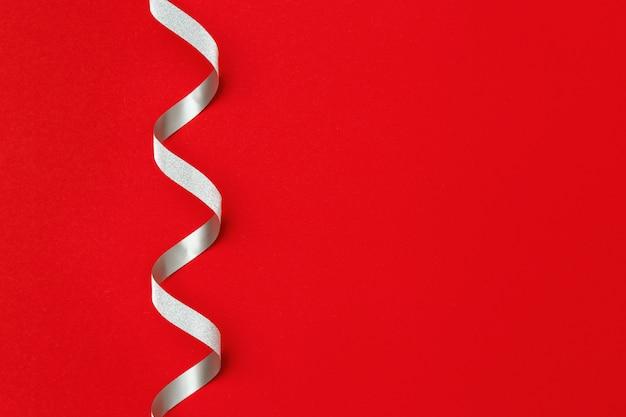 Декоративная серебряная лента на ярко-красном фоне с копией пространства. рождественский декор праздничное оформление. поздравительная открытка
