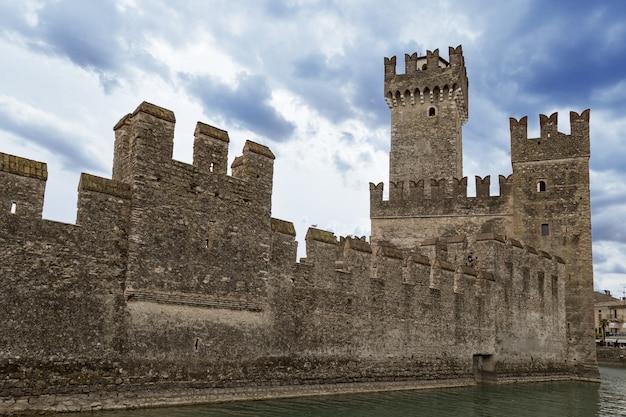 Замок скалигер является исторической достопримечательностью города сирмионе в италии на озере гарда. вид на старый замок в небольшом итальянском городке.