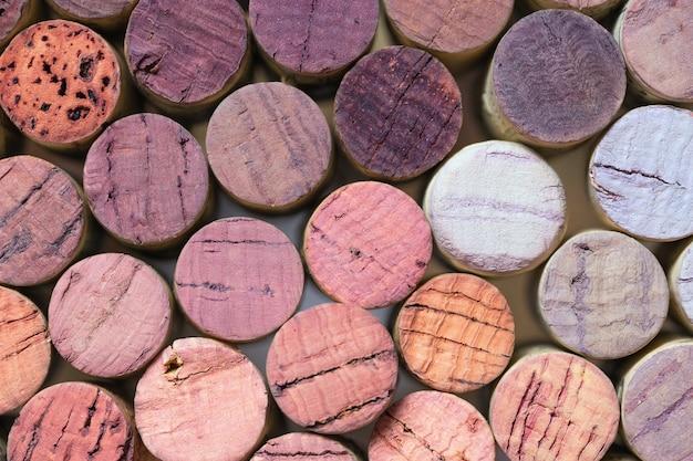 使用済みのワインのコルクの壁のクローズアップ。ワイン色のコルクの背景。テクスチャのワインのコルク。古いコルクのワインの階段。