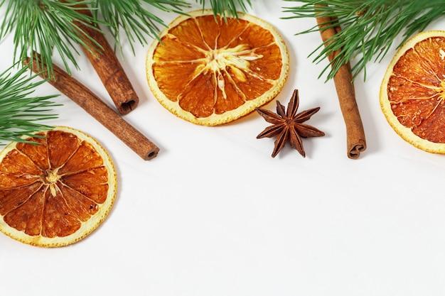 Сушеные ломтики апельсинов и палочки корицы на светлом фоне