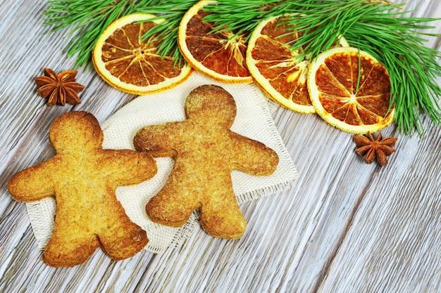 ジンジャーブレッド男性、乾燥オレンジ、アニスの星、木製のテーブルに常緑の枝