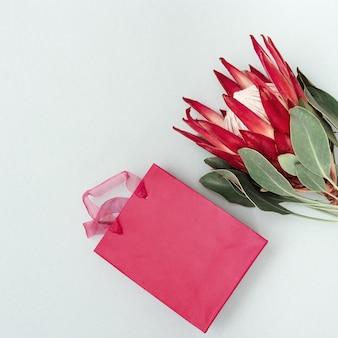 大きな美しい植物と青い表面にピンクのギフトボックス