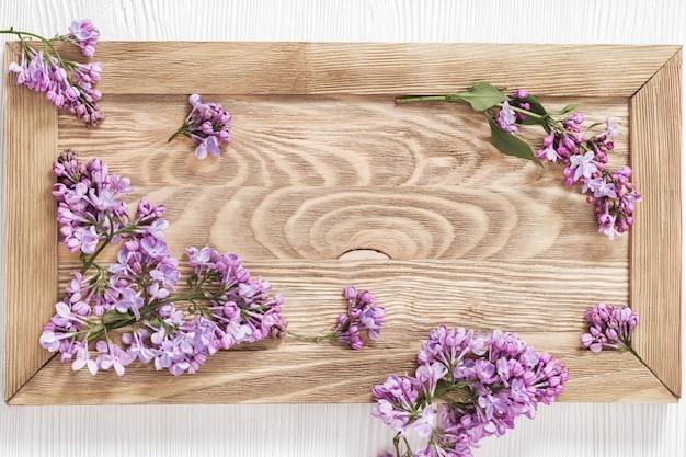 木製フレームにライラックの花の枝。ライラックの春の新鮮な小さな花。コピースペースと花の境界線の背景。