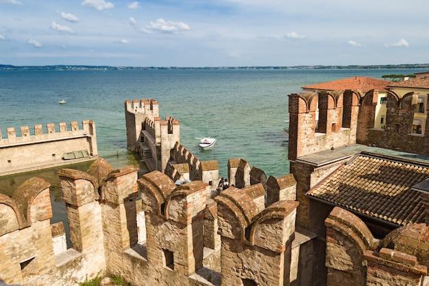 中世の城の古い壁とカルダ湖ビューの夏の風景。イタリアの小さな町シルミオーネ