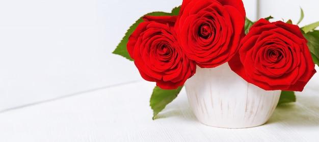 Красные розы цветы в белой керамической вазе. букет из цветущих цветов.