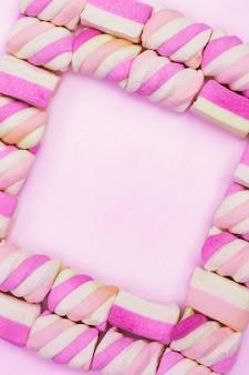 Кадр из сладкого зефира на розовом фоне. романтическая рамка
