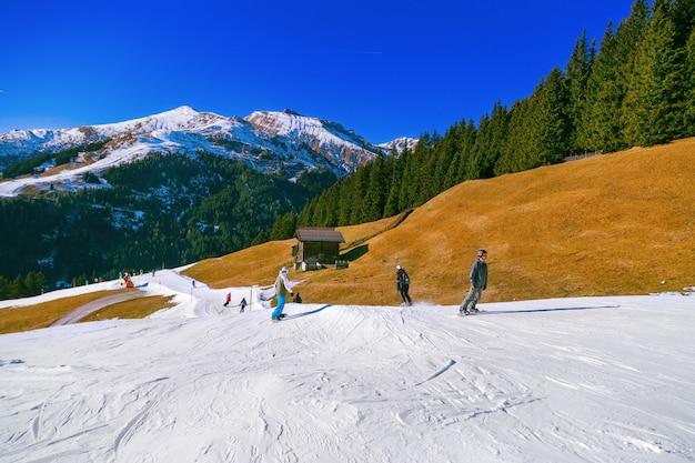 美しい山の風景。スキーヤーは丘を下ります。アルプスでスキーをするアクティブな休日。バックグラウンドで雪で覆われた山頂