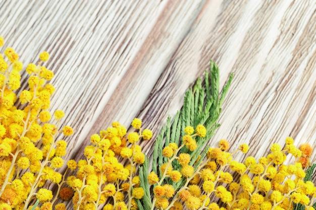 花の境界線を持つ木製の背景。咲くミモザの小枝は木のテーブルにあります。花の背景。
