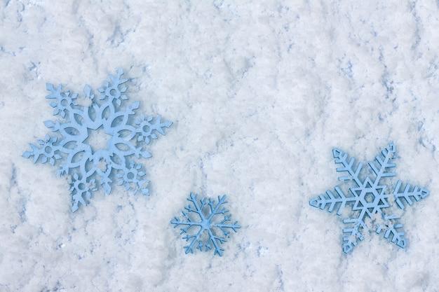 Открытка с новым годом и рождеством с голубыми деревянными снежинками на фоне снега с копией пространства. квартира лежала. вид сверху.