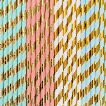 ストライプパターンゴールド色のカラフルな紙カクテルストローから明るい背景