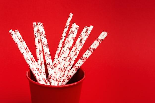 赤の金属製のバケツで冬パターンでストローを飲む明るい紙