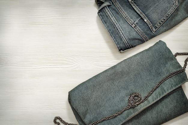 デニムの服をセットします。ブルージーンズとコピースペースを持つ白い木製の背景に小さなカジュアルバッグ。レトロ調。平干し。上面図。