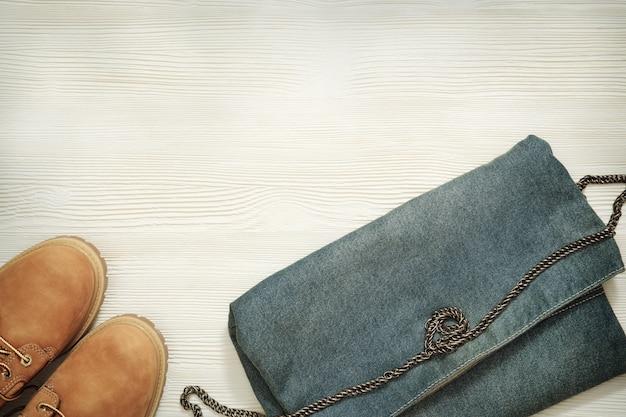 トレンディな靴とコピースペースを持つ白い木製の背景にデニムのハンドバッグ。女性のカジュアルな服装。レトロ調。平干し。上面図。