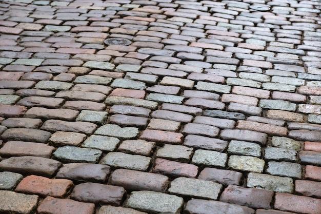 «натуральный брусчатый гранит на дороге. брусчатка в старом городе. мокрый валун».