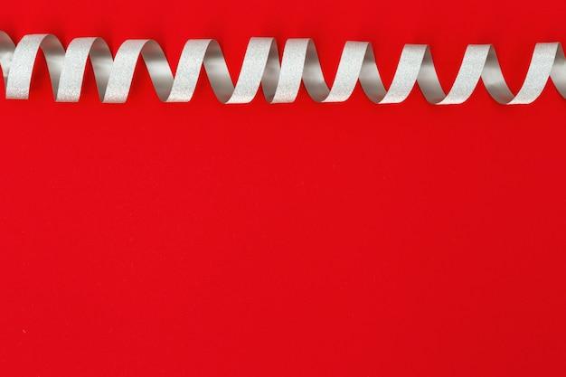 コピースペースで赤い紙の背景に明るいシルバーリボン。バレンタインの日やクリスマスの装飾のグリーティングカード。