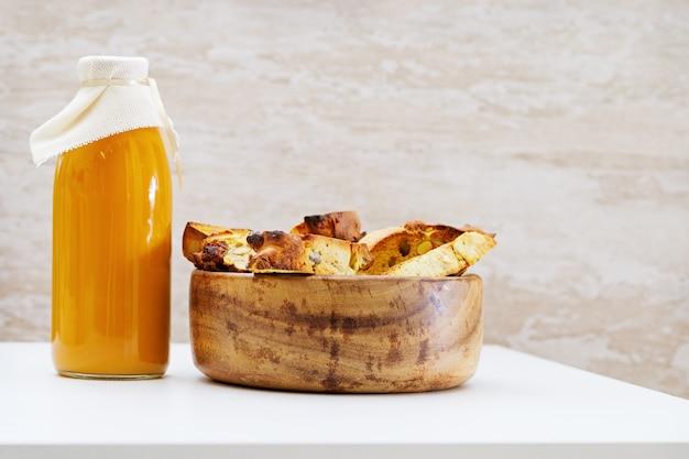 ナッツ、天然フルーツジュースのガラス瓶とイタリアのドライビスケットビスコッティ。シンプルな料理、素朴なスタイル。