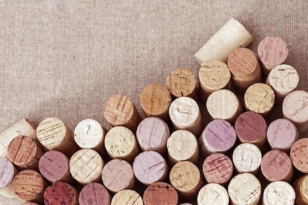 テーブルの上のワインのボトルから色とりどりのコルク栓。天然コルクの列