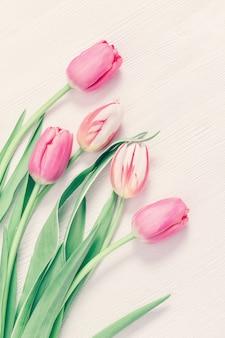 テキストまたはお祝いのコピースペースを持つ白い木製テーブルに柔らかいピンクのチューリップ。春の時間の概念のグリーティングカード。パステルカラー。垂直フォーマット、上からの眺め。