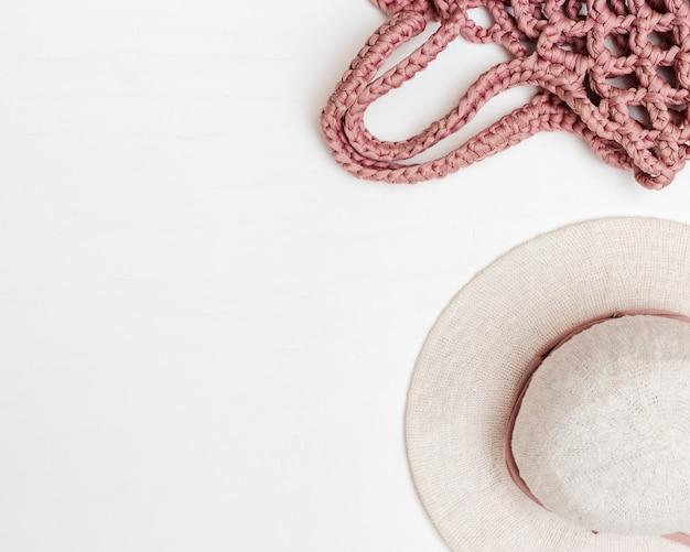 Пляжная женская шляпа и розовая сумка ручной работы на светлом фоне бетона. вид сверху. копировать пространство