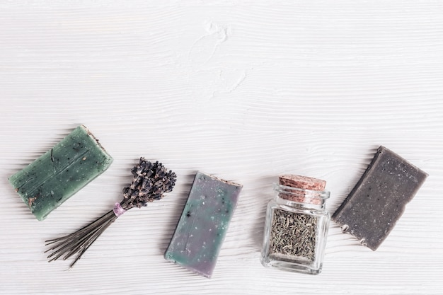 美しさとスパのコンセプト。自然な香りのハーブと白い木製の背景にラベンダーの手作り石鹸。コピースペースを持つ平面図と平面レイアウト。