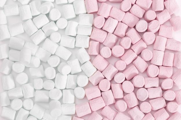 マシュマロパターンの背景。マシュマロピンクと白のパステルカラー、甘い食べ物。上面図。