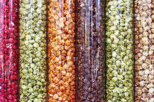 マルチカラーポップコーンの背景。ガラス容器に赤、黄緑、オレンジのポップコーン。