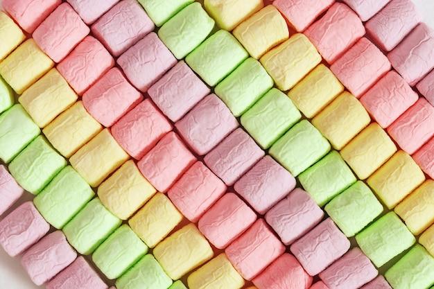 明るくカラフルなマシュマロからの背景。マシュマロの斜めの行。柔らかいお菓子の幾何学模様。
