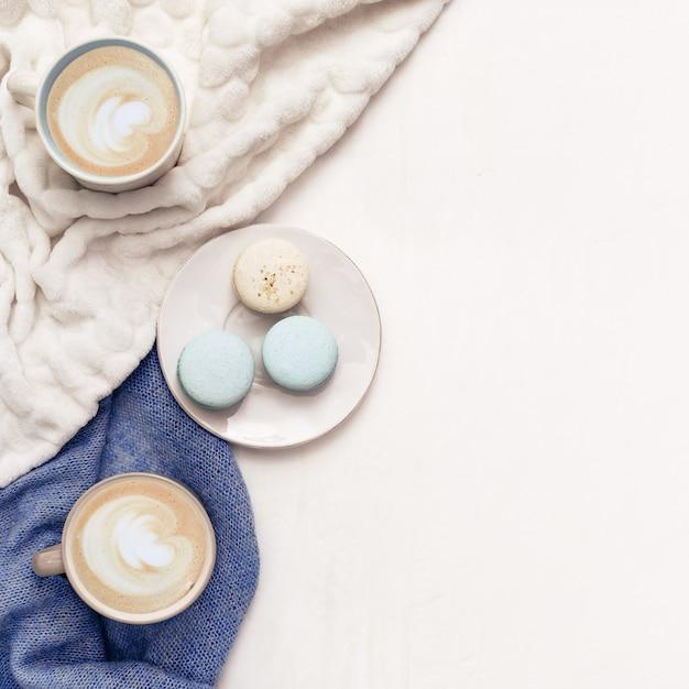 カプチーノアート、甘いマカロン、暖かい服、ライフスタイルの背景の平面図です。朝は自宅でホットコーヒー。冬のコンセプト。