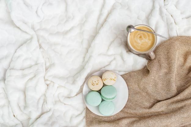 カップコーヒーカプチーノとコピースペースと明るい背景においしい甘いマカロン。冬の朝のコンセプト、リラックスの時間。上面図。平置き