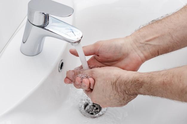 Мытье рук с антибактериальным мылом в горячей воде для защиты от распространения коронавирусных микробов