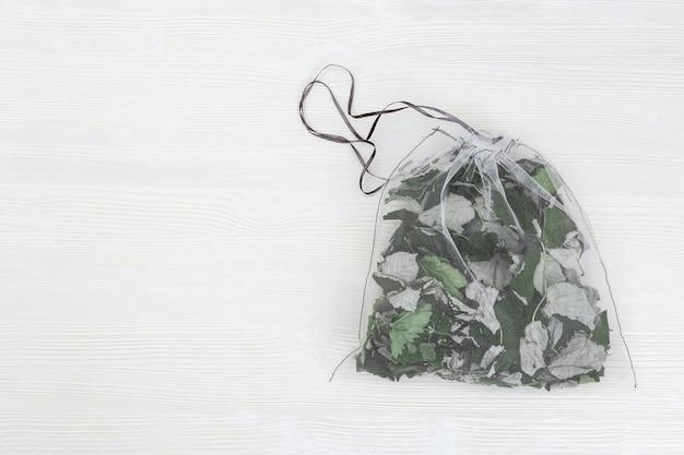 テキスタイルバッグのブラックカラントの白い木製の乾燥した若い葉のエコナチュラルバッグでハーブティーを醸造するための有用な芳香性ハーブ。プラスチックの無料コンセプト。
