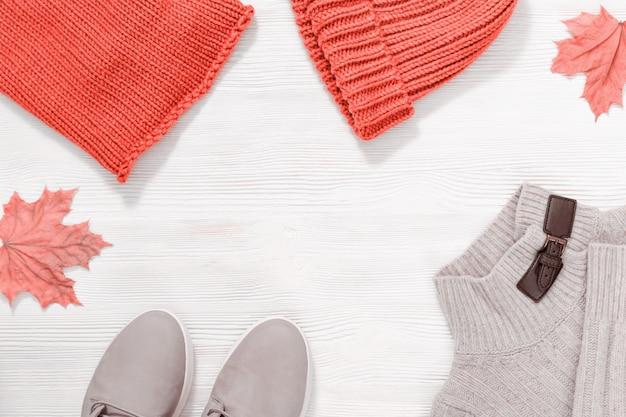 秋の天候のための女性のカジュアルなピンクの服、ファッションレザーシューズ、暖かいニットジャンパー、キャップ、スカーフのトレンドカラー。上からの眺め。コピースペース。