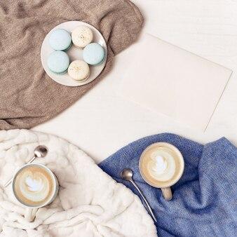 大きなマグカップのカプチーノコーヒーアートと暖かいニット服を着たホームテーブルの甘いマカロン。朝の温かい飲み物を飲むための居心地の良い環境。フラット横たわっていた。