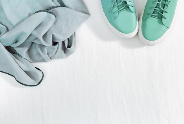 Теплый платок и туфли цвета тиффани на белом бетоне. мода и дизайн теплой одежды. вид сверху. квартира лежала. копировать пространство