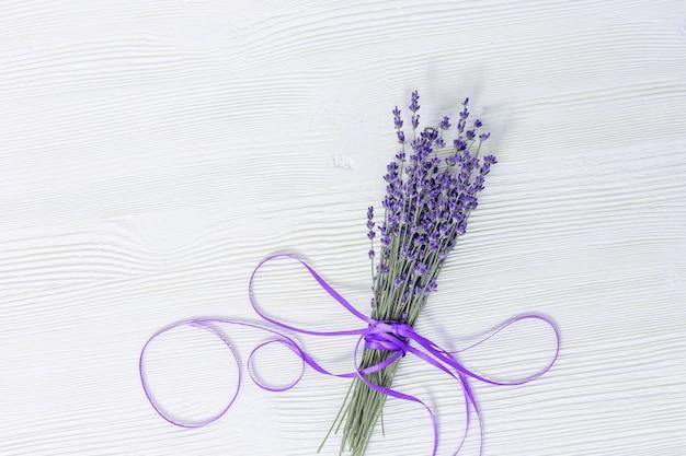 白い木製の表面にラベンダーの花を持つ素朴な背景。セレクティブフォーカス。