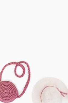 女性とスタイリッシュなピンクのバッグの帽子とビーチの夏の休日の背景。休暇の概念。コピースペース付きの縦書き形式。