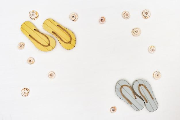Летняя обувь на белом фоне. пляжные шлепанцы серого и желтого цвета.