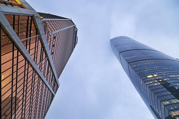 Вверх по взгляду современных зданий от стеклянного материала покрашенного синью. два высоких дома и голубое небо. высотные здания простираются до небес.