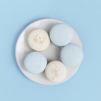 ビスケットマカロンと白い皿の上から見る。甘くておいしいデザートアーモンドクッキー。最小限のスタイル構成。