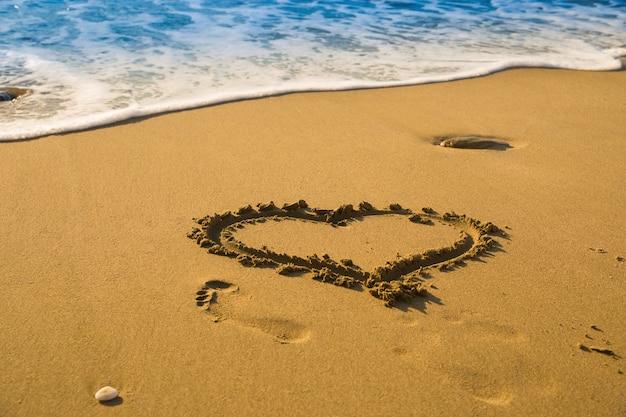 Рисование сердца на пляже песок на пляже с морскими волнами в. выборочный фокус. прекрасный пустынный пляж. след человеческой ноги на песке.