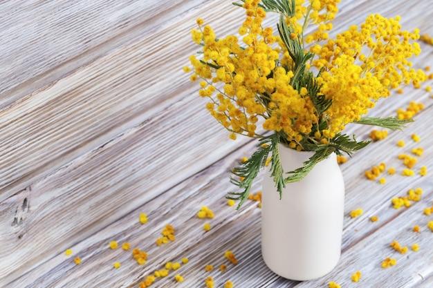 古い木造のミモザと花瓶。白いセラミック花瓶の黄色のふわふわの花アカシアの束は素朴な静物です。セレクティブフォーカス。