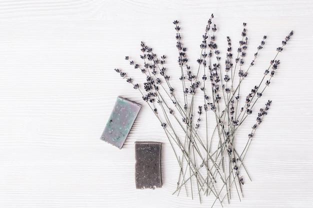 天然オーガニック食材を使った手作り石鹸バー、コピースペース付きの白い木のテーブルにラベンダーの花を乾燥させました。アロマセラピー、美容スパ。上面図。