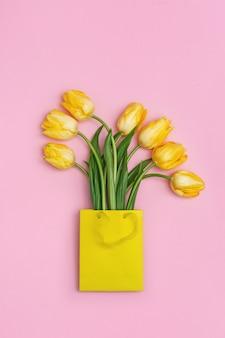 ピンクの表面に紙のギフトバッグに黄色いチューリップの春の花。コピースペースと花の自然の新鮮な花束。明るい色と最小限のスタイル。上面図。フラットレイ