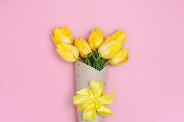 リボン付きクラフト紙の黄色のチューリップ。コピースペースと明るい春咲く花。フラット横たわっていた。